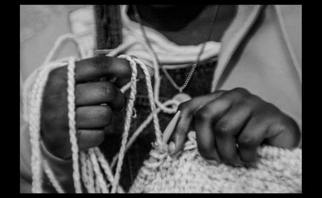 A black and white image of hands knitting wool