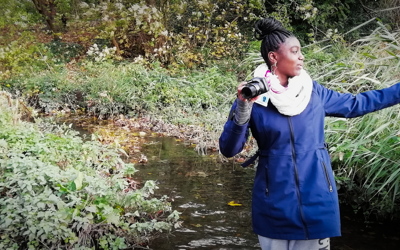 Young person in a river taking a photograph