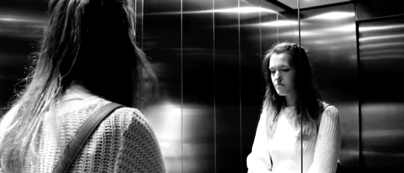 Black and white image of a young woman looking in a mirror