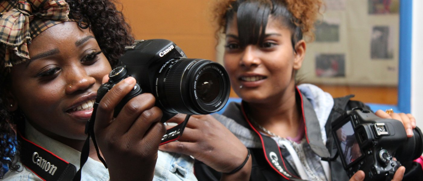 Two teenage girls using cameras