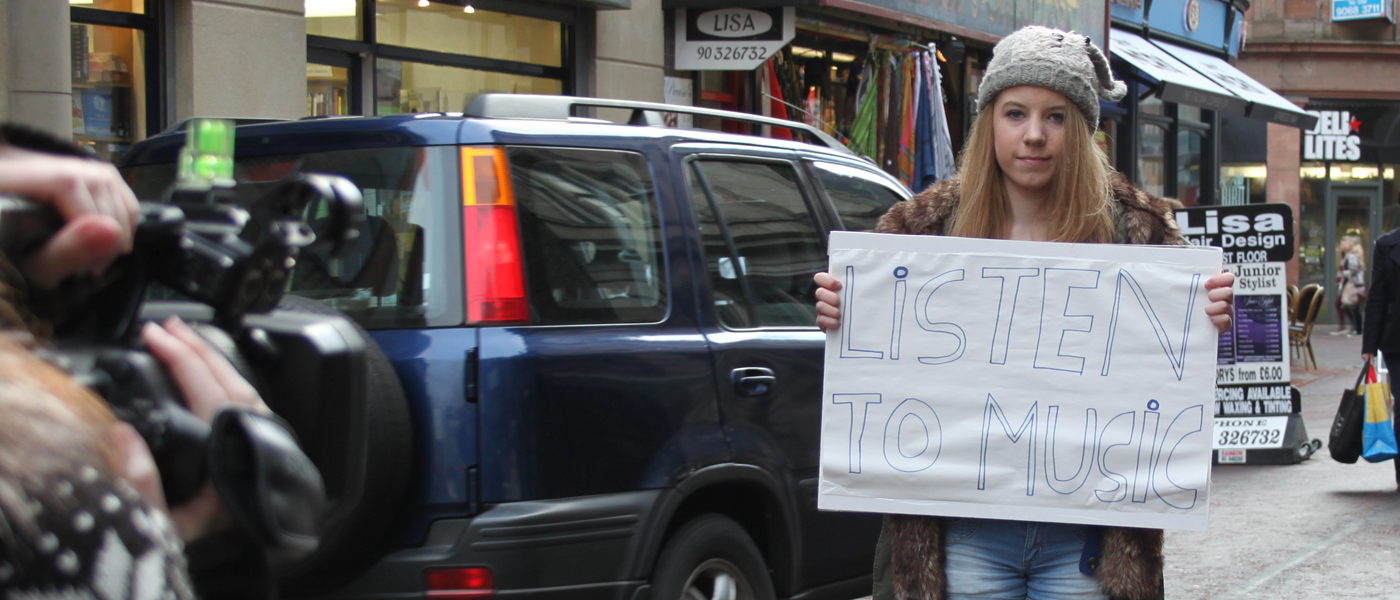 Young woman holding up a sign with listen to music written on it